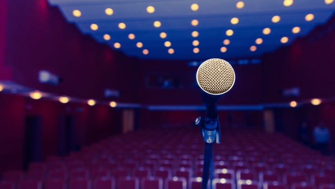 microphone on a background of dark hall with seating for spectators. chairs for the audience