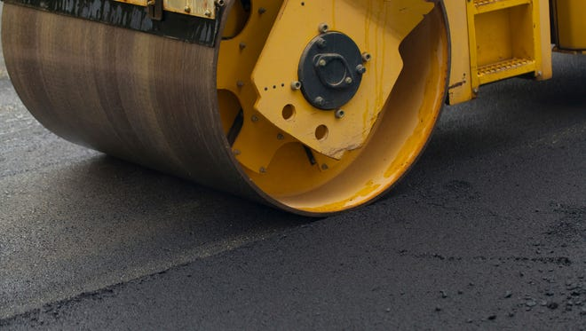 Road roller flattening new asphalt on street. There is wide copy space.