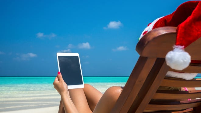 Blank empty tablet computer in the hands of women in santa hat on the beach