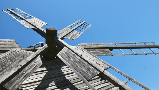 Sails of one old vintage wooden windmill over clear blue sky, close up, low angle view