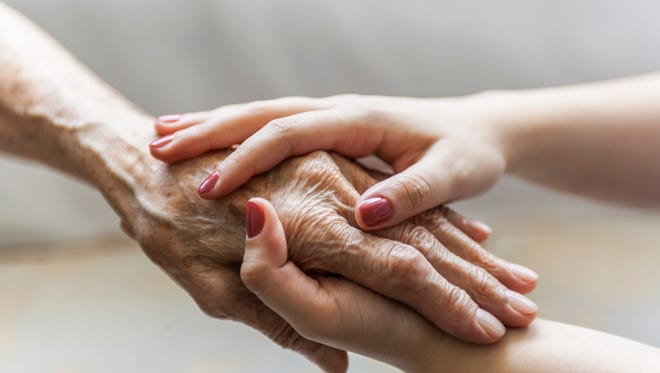 Young woman is holding a senior woman's  hand for help.