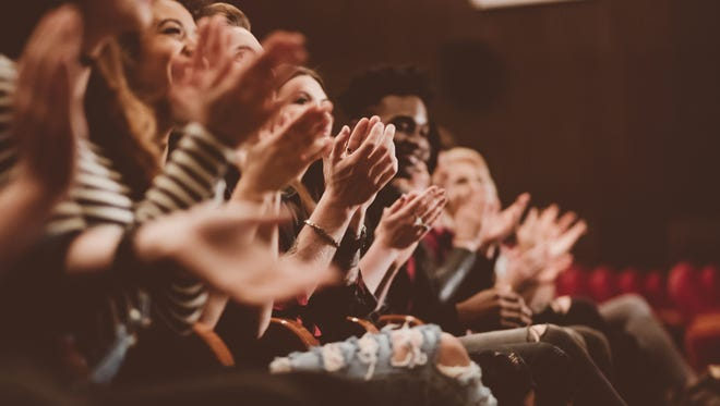 Group of people clapping hands in the theater,
