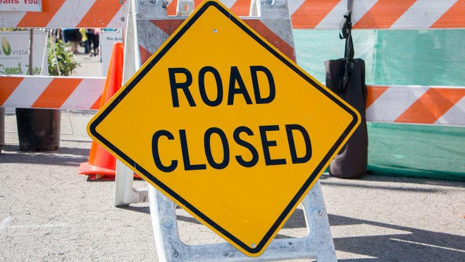 Road Closed Sign with Barricade in Background