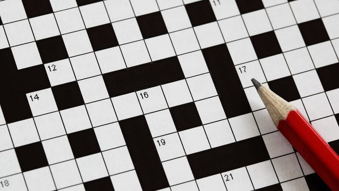 Solving a crossword puzzle with a red pencil.