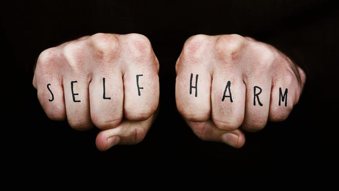 Self Harm written across the knuckles of two clenched fists.