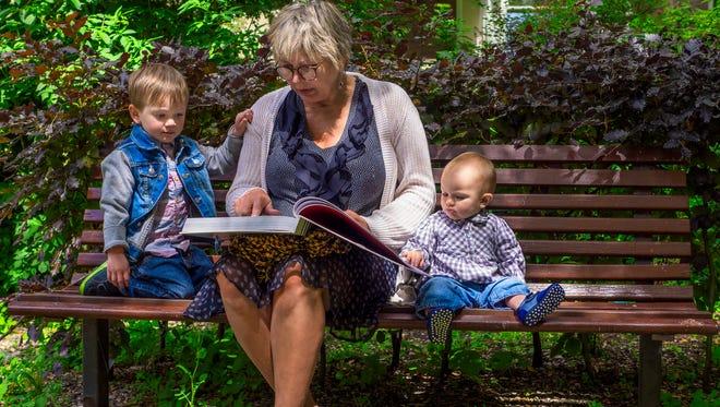 Grandmother reading to her grandchildren in the park