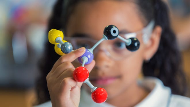 Close up of African American female elementary age student holds a model of the molecular structure. Focus is on the model, the girl is blurred in the background.