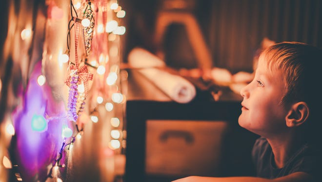 Young boy is getting ready for Christmas. The main focus are Christmas lights. The boy is looking at the lights