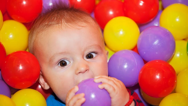 Toddler enjoying a ball pool at the indoor playground