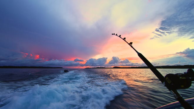 A sun sets off the back of a speedboat with a fishing rod in the foreground