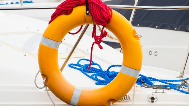 Yachting blue and red coiled rope with orange lifebuoy on deck of sailboat, part of yacht, safety travel