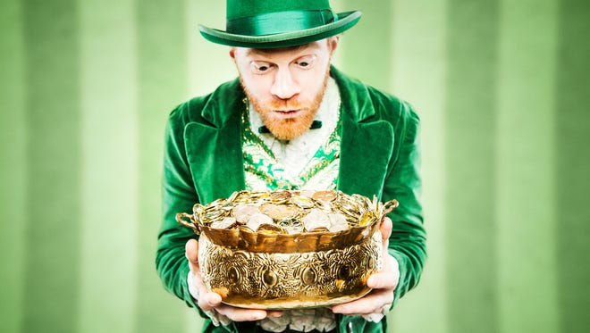 A stereotypical Irish character all ready for Saint Patricks day.  He holds up a pot of gold looking at it with wide excited eyes.  Geen striped wallpaper wall behind him.  Horizontal image with copy space.