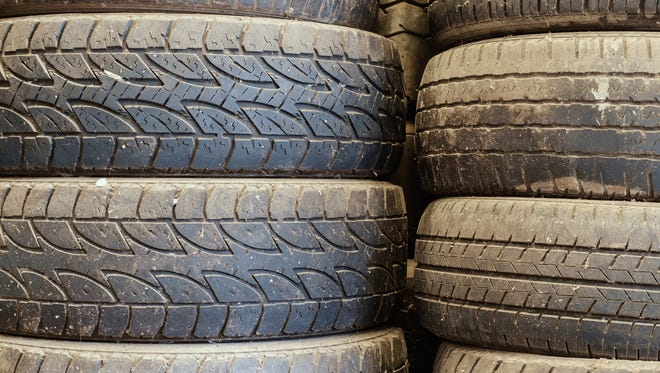 Old used car tires stacked up in the storage area for disposal, repairs or reuse