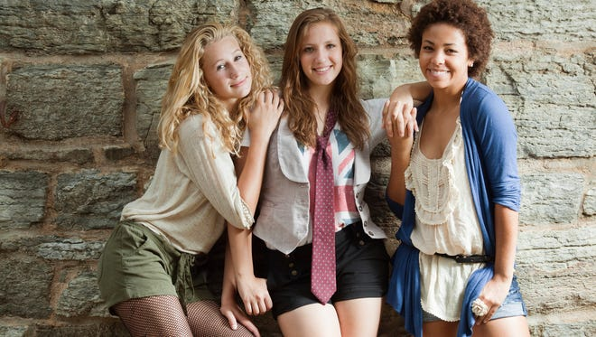 """""""Subject: Three teenage girls standing by an old stone wall, holding hands, leaning on each other, looking cool and cute in funky casual clothes, and smiling for the camera."""""""