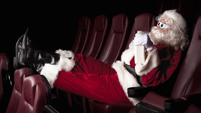 Santa Claus enjoys his day off at the movie theater.