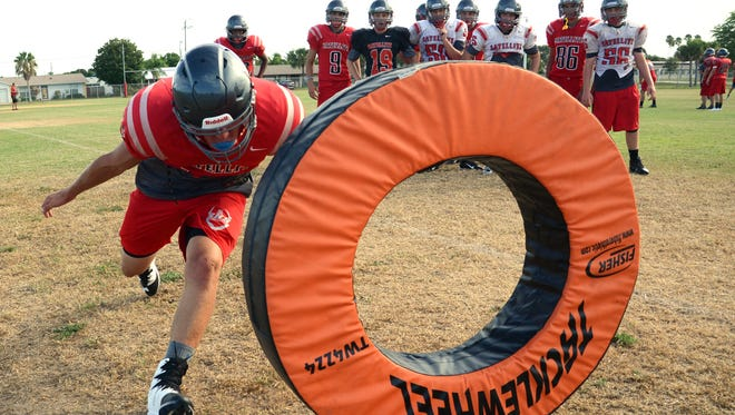 Members of the Satellite High football team go through tackling drills during practice Thursday afternoon.