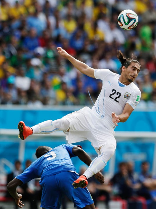 Italy's Mario Balotelli gets underneath Uruguay's Martin Caceres as he tries to head the ball during the group D World Cup soccer match between Italy and Uruguay at the Arena das Dunas in Natal, Brazil, Tuesday, June 24, 2014. (AP Photo/Petr David Josek)