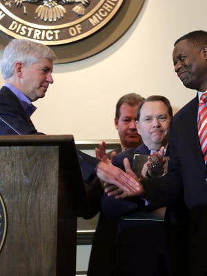 Gov. Rick Snyder, left, and Emergency Manager Kevyn Orr shake hands during a press conference following Judge Steven Rhodes' approval of Detroit's historic restructuring plan on Friday November 7, 2014 at the Federal Courthouse in downtown Detroit.