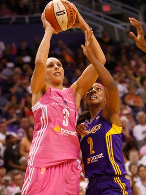 Mercury guard Diana Taurasi shoots while defended by Los Angeles Sparks guard Candice Wiggins at US Airways Center on Tuesday. Mercury players wore pink uniforms to promote breast-health awareness.