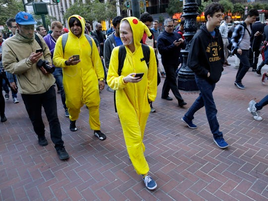 "Ashley Paramore, center in yellow costume, and Vikram Matange, center left in yellow costume, are dressed as ""Pokemon Go"" characters during a gathering of players Wednesday, July 20, 2016, in San Francisco."