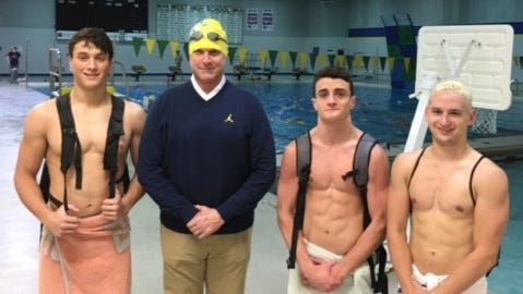 Jim Harbaugh, with swim cap and goggles, poses for a photo with Oliver Martin, left, and two of Martin's teammates last week in Iowa City.