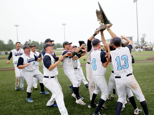 West Bend West players hoist the trophy and celebrate