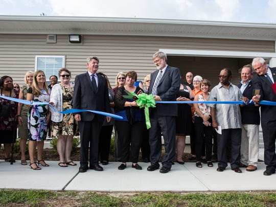 Jim Porter, center, President of the Somerset Committee for the Homeless cuts the ribbon on a new homeless shelter in Princess Anne on Wednesday, Sept. 27, 2017.
