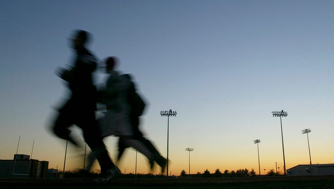 In this Thursday, Jan. 22, 2004 file photo, students jog around a stadium at sunset in Bowling Green, Ky. A large, international study released on Monday, Oct. 10, 2016, ties heavy exertion while stressed or mad to a tripled risk of having a heart attack within an hour. (Clinton Lewis/ Daily News via AP)