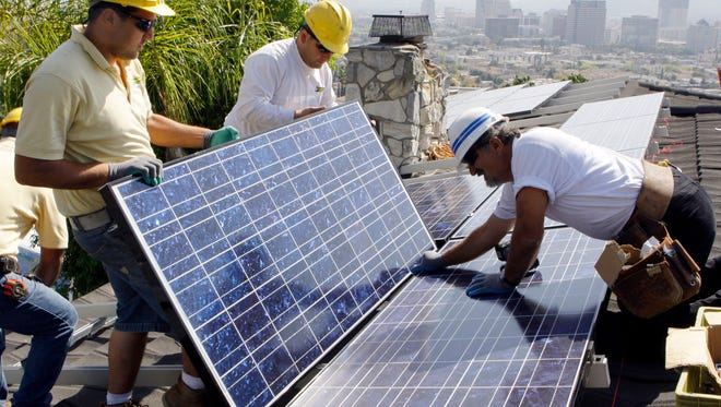 Installers from California Green Design install solar electrical panels on the roof of a home March 23, 2010, in Glendale, Calif. The Obama administration announced a plan July 19, 2016, to help middle-class and low-income communities put solar panels on their roofs.