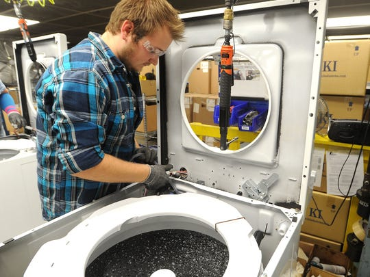 Taylor Zerney of Berlin connects hoses and wires in a washing machine at Alliance Laundry Systems in Ripon. The company has about 1,700 employees in the city.