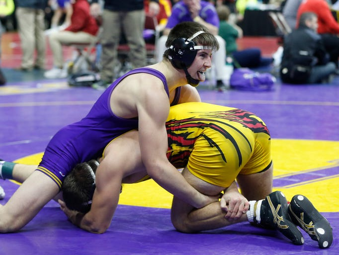 Indianola's Kade Kolarik (top) reacts as he wrestles