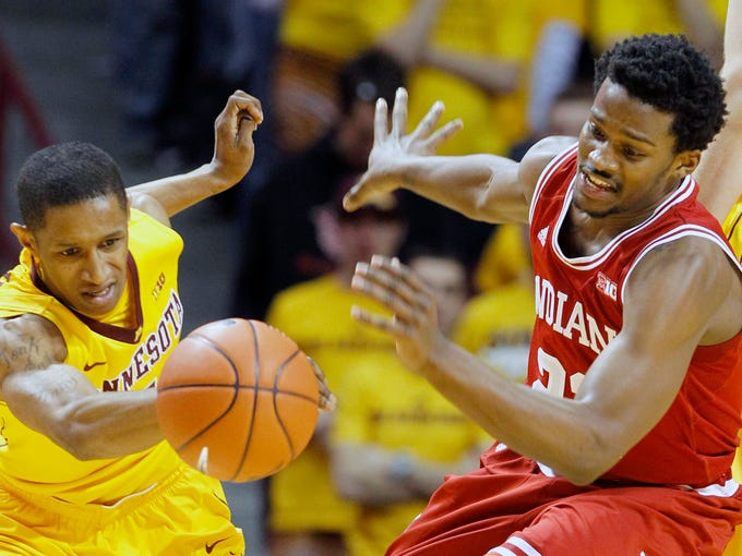 Minnesota guard DeAndre Mathieu, left, and Indiana guard Stanford Robinson, right, chase a loose ball during the first half of an NCAA college basketball game in Minneapolis, Saturday, Feb. 8, 2014. (AP Photo/Ann Heisenfelt)