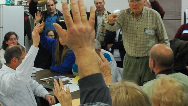 Robert Andreason, right, counts votes during show-of-hands balloting at the Republican caucuses at Trinity Lutheran Church in this February 5, 2008, file photo.