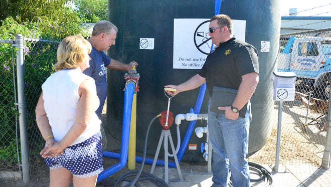 Sgt. Mike Yandell, right, shows eastside Porterville residents how to use a new water tank that will help provide  water to as many as 500 residents. Photo taken in 2013.