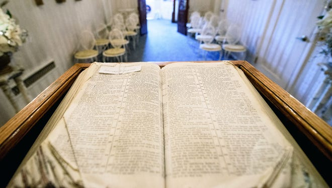 A tattered bible turned to 1 Corinthians, a chapter of the Bible that describes love, sits on the pulpit at Chapel of the Bells wedding chapel.