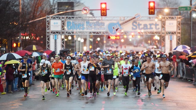 Spectators shelter themselves from the steady rain as runners flood past the starting line to begin the 2016 Mississippi Blues Marathon.