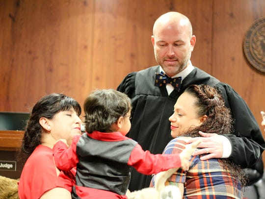 Judge Timothy McCoy hugs a family after finalizing