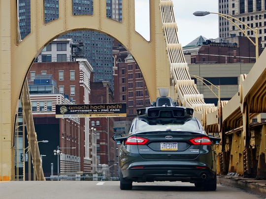 A self driving Uber car drives across the ninth street