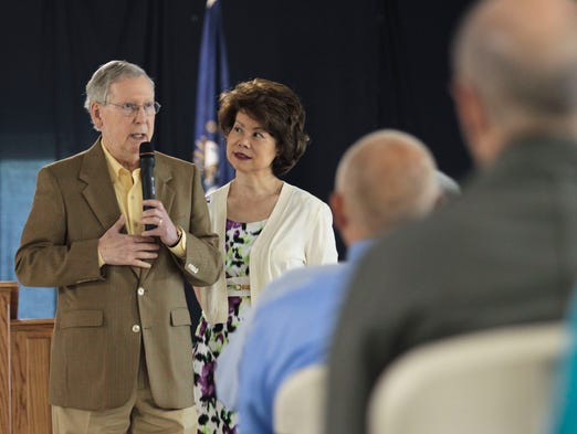 """Sen Mitch McConnell spoke to a small audience in the Pork Producer's Building at the Central Kentucky Ag/Expo Center in Liberty, Ky. Saturday morning. At right is McConnell's wife Elaine Chao, former U.S. Secretary of Labor. McConnell has told The New York Times in March that as far as conservative outside groups challenging him and other GOP incumbents, """"I think we are going to crush them everywhere.""""  May 10, 2014"""