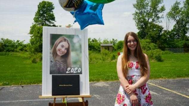 """Meadow Montessori School graduate Elizabeth Harrigan celebrates her achievement during a """"drive-by"""" celebration June 5 on the campus, where members of the school community shared gifts and cards with  the graduating class."""