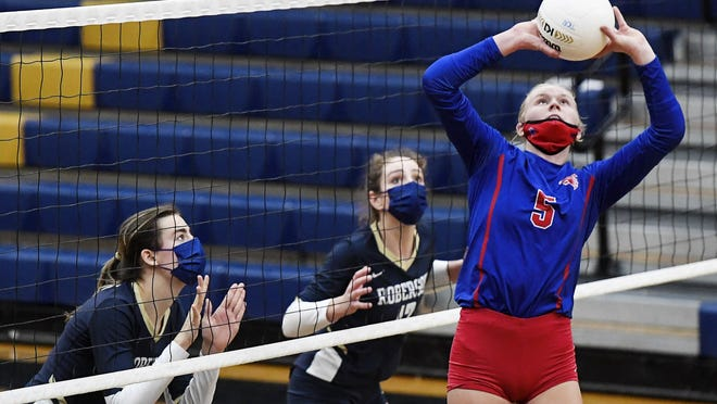 West Henderson's Malia Moore sets the ball in Thursday's match at T.C. Roberson.