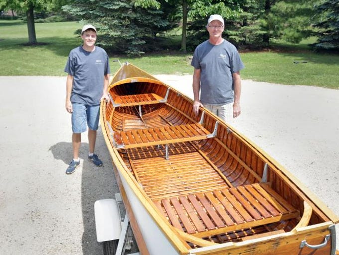 Dean Wingert, 19, left, and his dad Dale Wingert, stands by their 1930s-era Richardson Boat Saturday June 14, 2014 in Sheboygan Falls. A group of enthusiasts of the Sheboygan Falls made boats will be bringing their boats out to Wings 'N Wheels Sunday.