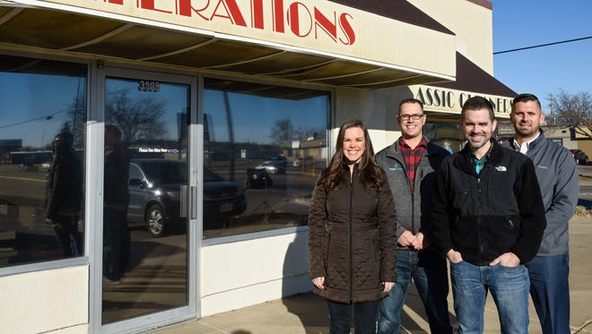 Abigail Lexen, Tim Fedders, Pastor John Sorell, and Galen Van Otterloo (left to right) pose for a portrait in front of the building that will be the permanent home of Arise Church. The church's previous home was in a middle school gym.