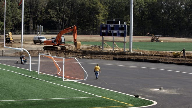 Workers install a new synthetic turf field at Suffern Middle School on Sept. 18, 2006. Ramapo Central school district residents will vote Tuesday on a proposal to fix the now-worn fields.