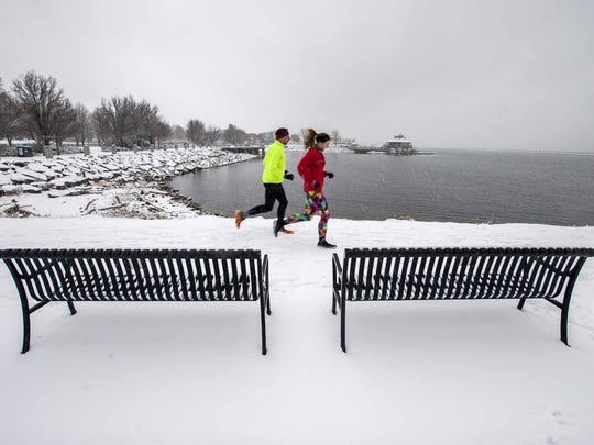 Runners cross fallen snow at Waterfront Park in Burlington
