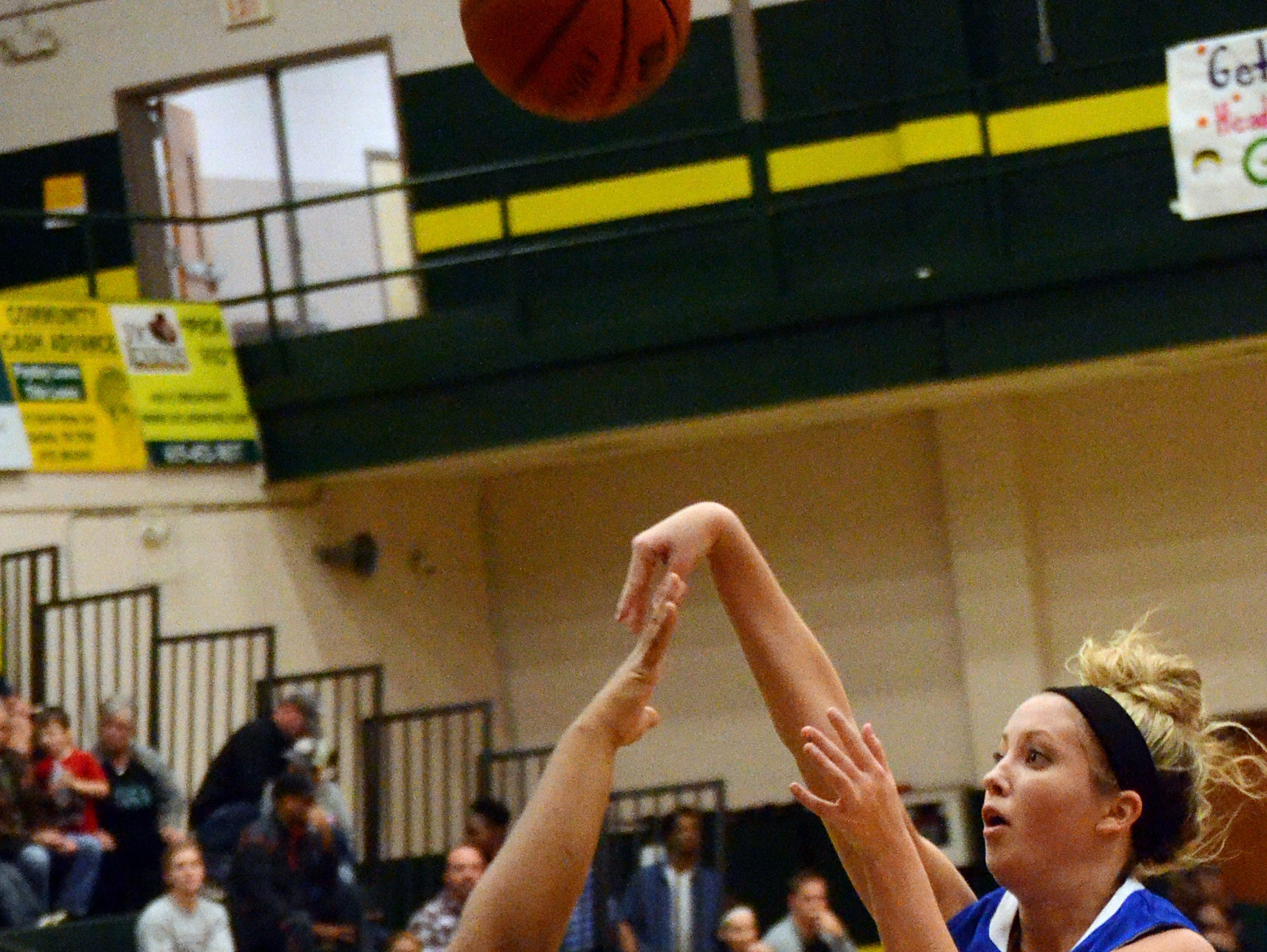 White House High senior point guard Alyssa Armstrong releases a second-quarter jump shot over the outstretched arm of Gallatin sophomore LaMonica Mintlow. Armstrong scored eight points.