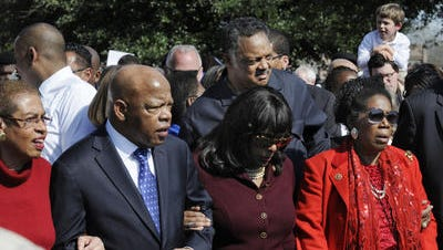 US Representatives John Lewis, D-GA, and Terri Sewell, D-AL, with Jesse Jackson, join other marchers along Alabama Avenue during the Bridge Crossing Jubilee on Sunday, March 9, 2014, in Selma, Ala.
