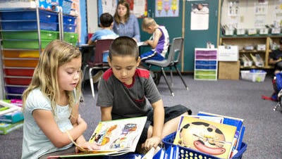 Burk Elementary School students Cameron White and Rudy Ochoa reads their book together in their classroom on March 31, 2015. Gilbert Public Schools needs to trim $11 million from its 2015-2016 budget. District is trying to preserve teacher positions and classroom equipment.