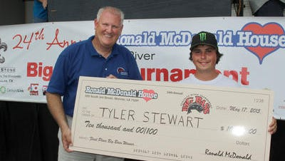 Tyler Stewart (right) accepts a $10,000 check from Ronald McDonald House Ouachita River Big Bass Tournament chairman Brad Burch (left) after winning the 2015 event.