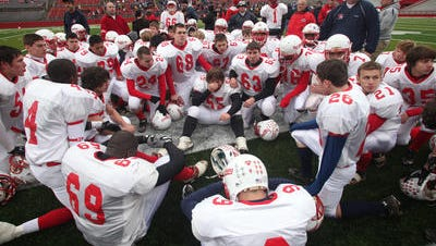 Dunellen High School football players gather on field at Rutgers Stadium following 2010 sectional championship loss to Shore Regional